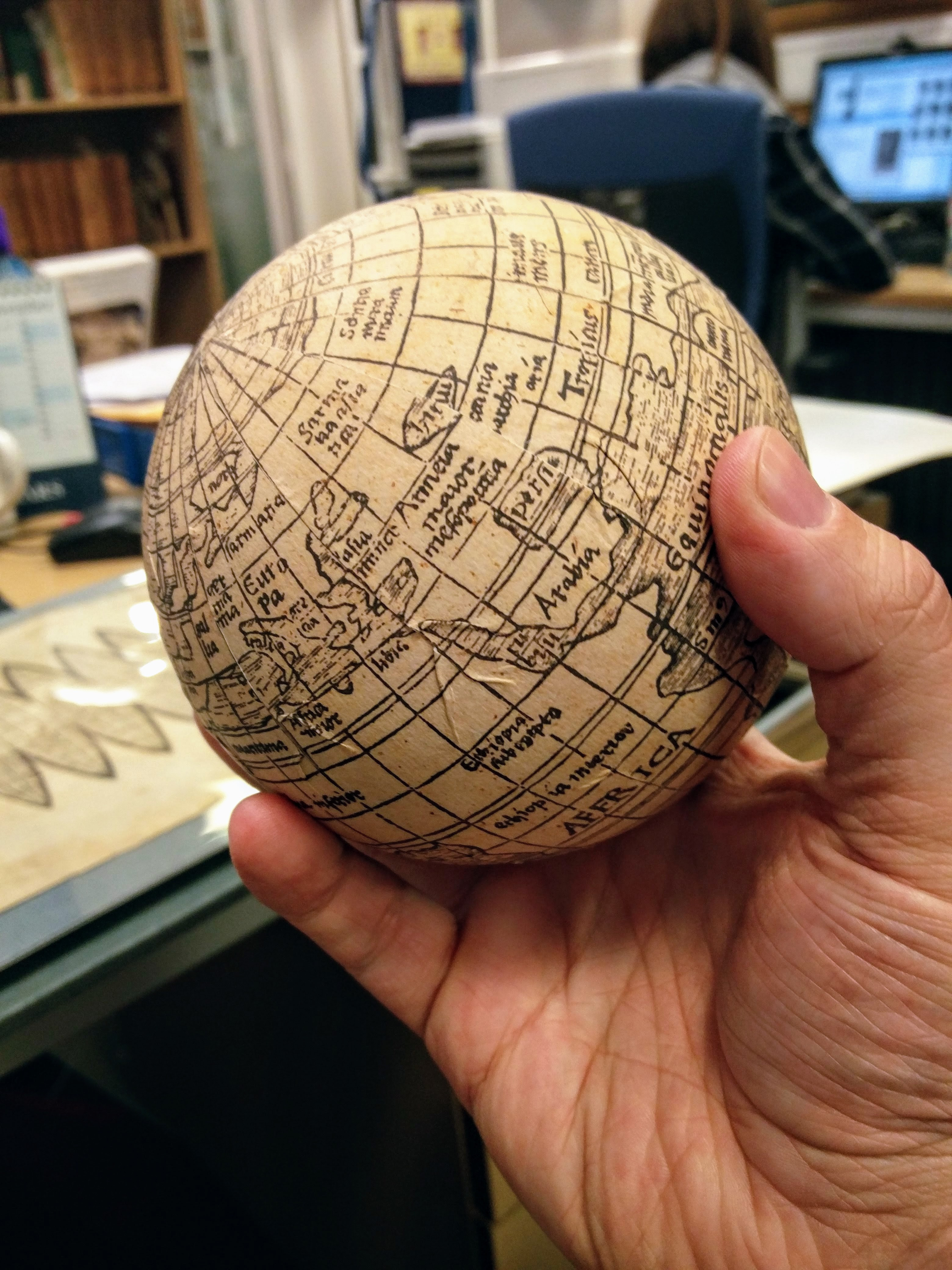 """Daryl holding the facsimile globe that the Christie's team made of the Waldseemüller map"""